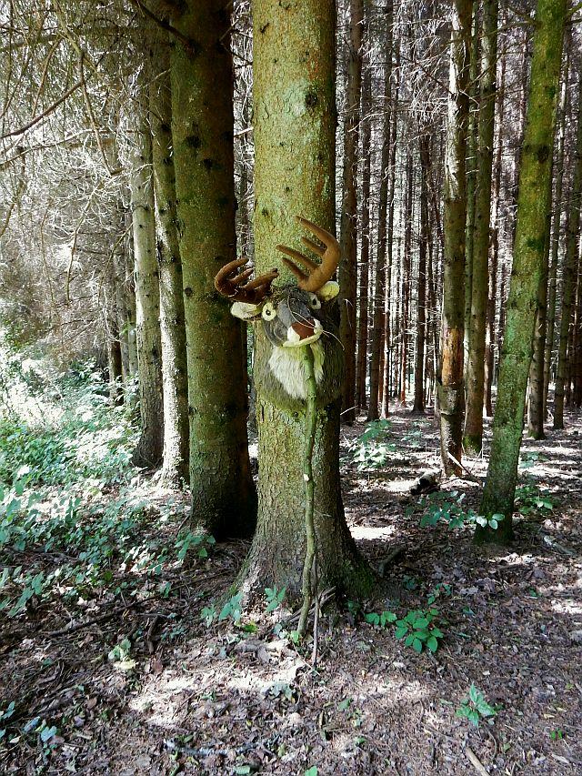 Ein Stofftier-Hirschkopf ist gegen einen Baumstamm gelehnt