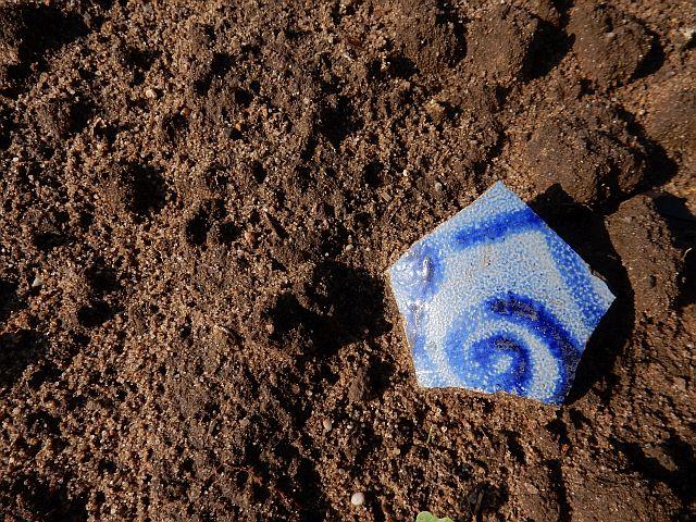 Blaugraue Scherbe eines Bembels liegt auf nacktem Boden