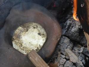 Ein tönernes Gefäss mit flüssigem Zinn steht am Feuer